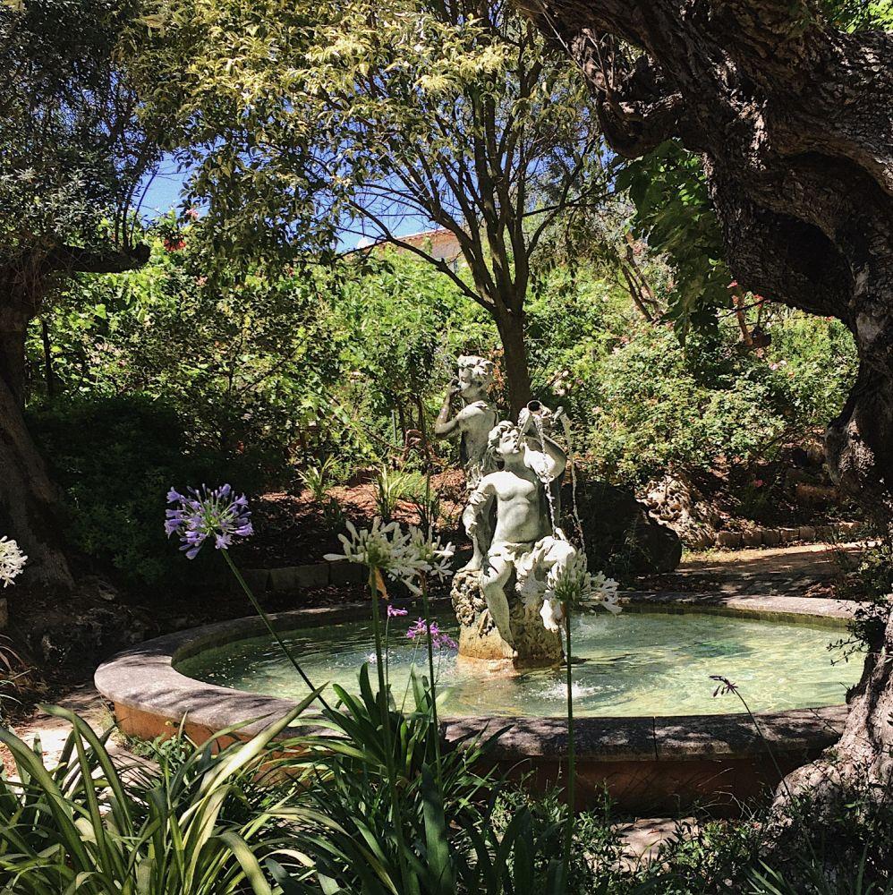 Bassin avec fontaine en statue de bronze.